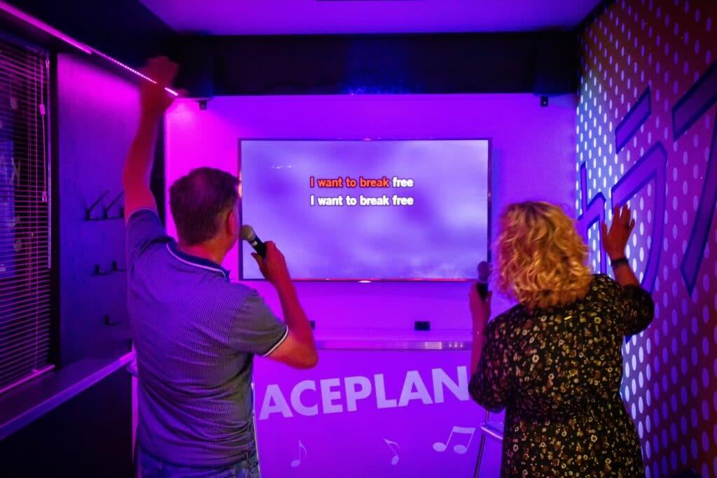 Twee zingende gasten in de karaokebar van Race Planet Amsterdam zingen hun favoriete karaoke lied tijdens een karaokesessie.