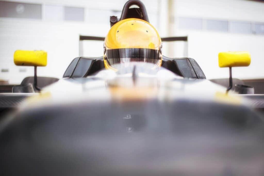 Coureur zit in de Formule RP1 om te gaan racen met helm op.