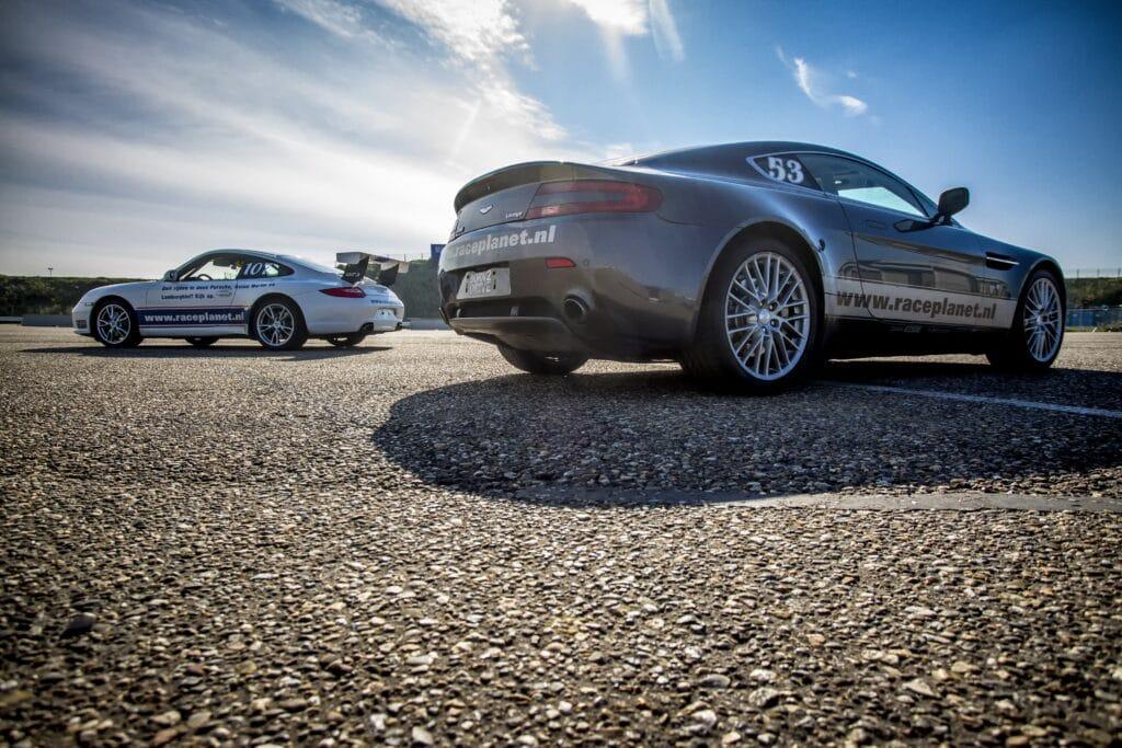 Porsche 911 en Aston Martin V8 Vantage op het paddock van Circuit Zandvoort tijdens een Race Experience van Race Planet.