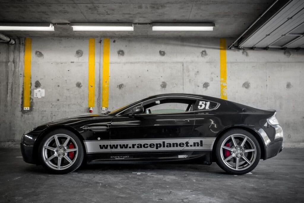 Zwarte Aston Martin V8 Vantage in een pitbox op Circuit Zandvoort tijdens een Bleekemolens Race Planet Race Experience