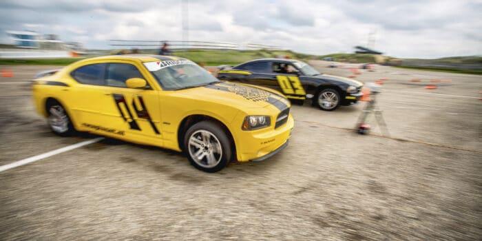 Twee deelnemers in Dodge Chargers strijden tegen elkaar in de dragrace om de overwinning op Circuit Zandvoort tijdens een Race Experience.