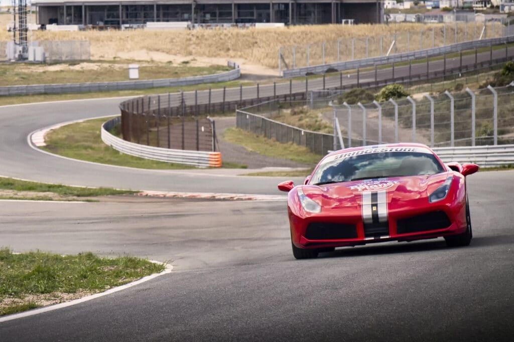 Rode Ferrari 488 GTB van Bleekemolens Race Planet op Circuit Zandvoort in de Slotemaker bocht tijdens een Race Experience.