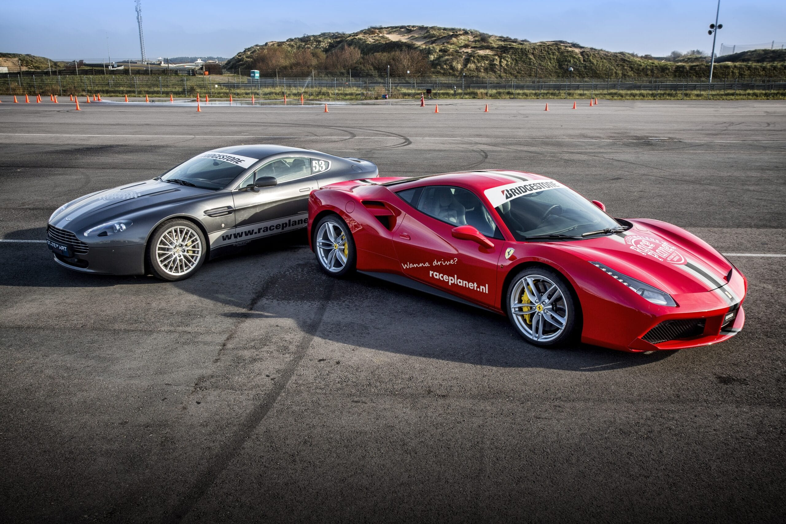 Grijze Aston Martin V8 Vantage en een Rode Ferrari 488 GTB staan om te rijden op Circuit Zandvoort tijdens een Race Experience van Race Planet