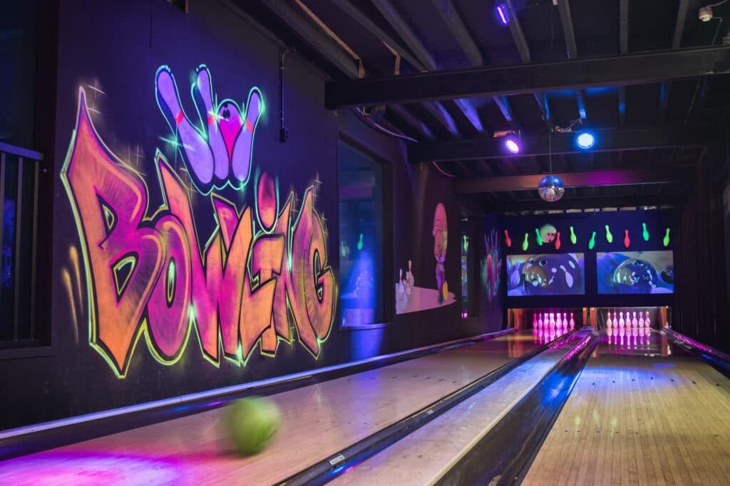 Bezoeker gooit een bowlingbal op de bowlingbaan bij Race Planet Amsterdam en Delft.