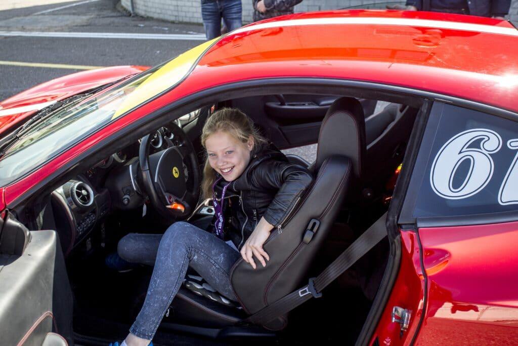 Meisje stapt uit een Ferrari van Race Planet op Circuit Zandvoort tijdens het Autorijden voor de Jeugd.