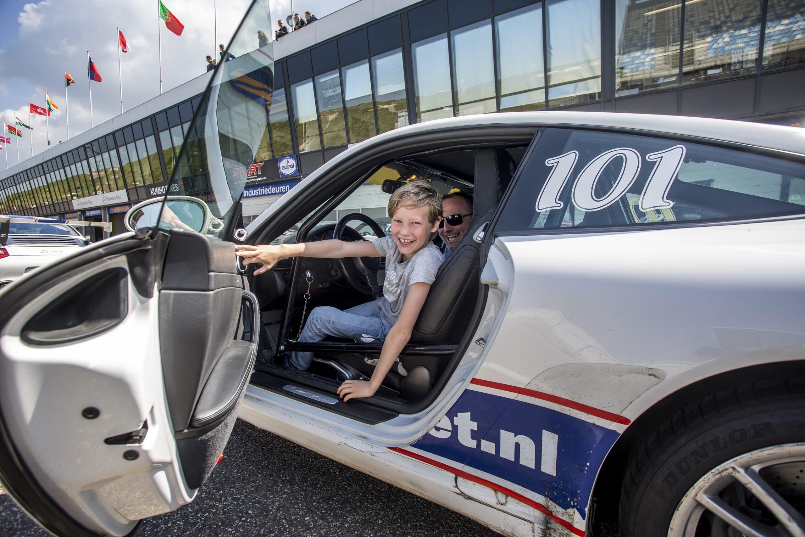 Jongen zit met grote glimlach achter het stuur van een Porsche 911 op Circuit Zandvoort tijdens het autorijden voor de jeugd.